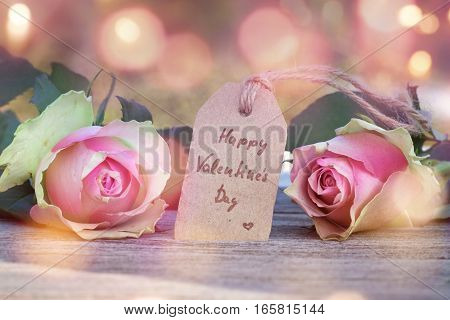 Roses with a greeting on a wooden table in front of a abstract background with bokeh for a valentines day card
