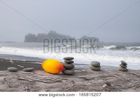 Stacked rocks and orange football on driftwood log with an ocean on the background