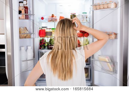 Rear View Of Young Woman Looking In Fridge At Kitchen