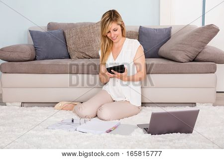 Young Woman Sitting On Carpet Calculating Tax Using Calculator At Home