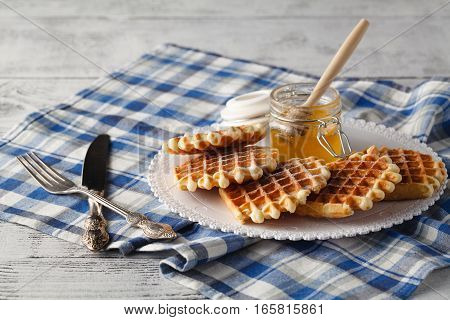 Breakfast with homemade wafers and honey in jar