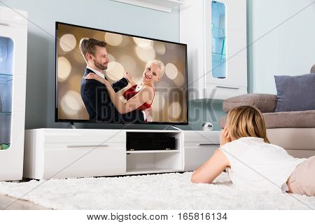 Young Woman Lying On Carpet Watching Romantic Movie On Television At Home