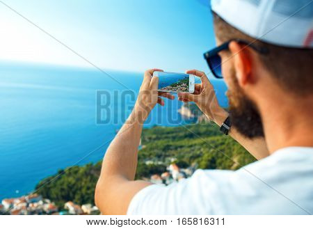 Man makes photos by a smartphone on the background of sea coast Adriatic sea Montenegro Balkans
