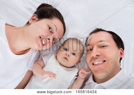 Portrait Of A Happy Family On White Bed
