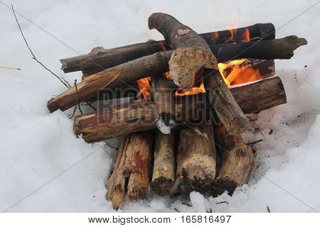 Camp fire in the winter with snow