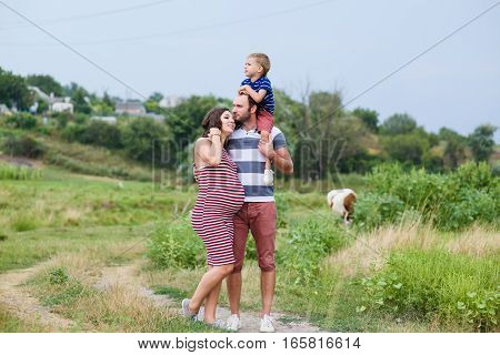 Happy pregnant family having fun in summer nature. A child on the shoulders of dad. Countryside, walk along rural road. Father and mother holding hands.