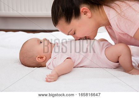Young Mother Kissing On The Stomach Of Cute Baby