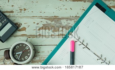 Concept of time management Planner & Organizer Notebook and timer and calculator on wood background