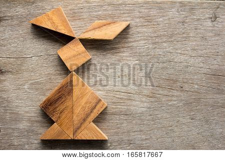 Chinese tangram puzzle in rabbit shape on wooden background (Concept for easter)