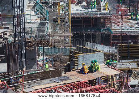 Laborers having a short break during work on modern construction site works in Dubai. Fast urban development concept.