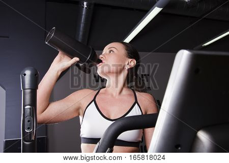 A young girl drinks water from a bottle during a workout at the gym .Cardio workout.