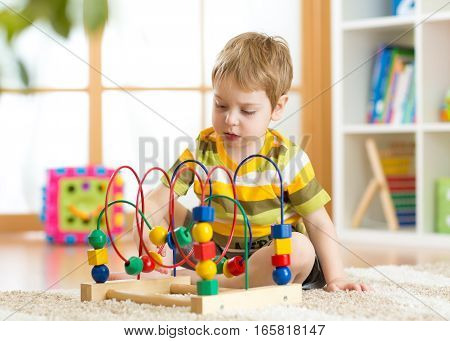 Little kid boy plays with a multicolored logical toy in nursery