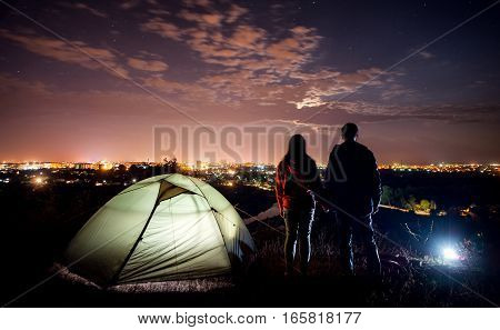 night camping near the town. a young couple holding hands and looking at night city