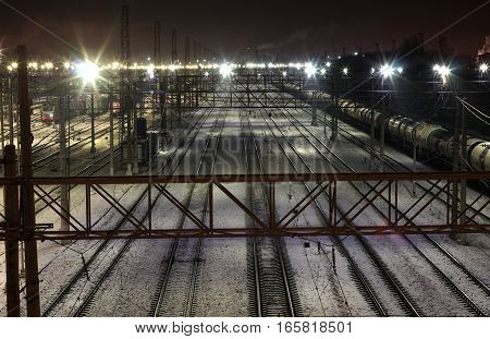 Winter railway junction station with a several light lamps.