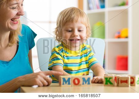 Mother teaches son child letters and words playing with cubes