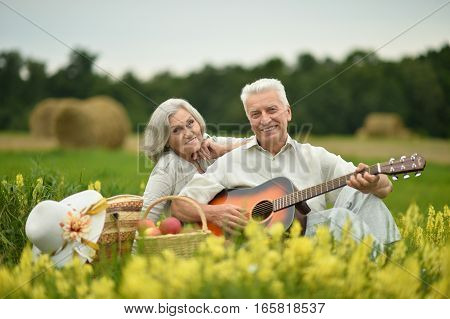 Senior couple with guitar at summer field with flowers
