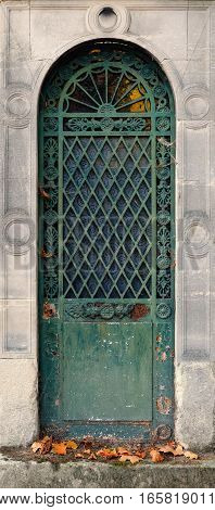 Closed steel door of an old crypt. The metal is of green and turqoise color and has a round arch. It is ornate with chiseled circles, floral decorations and a geometric check pattern.