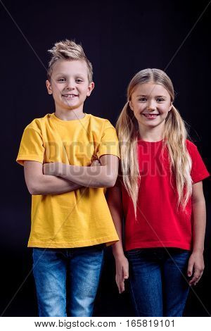 Portrait of smiling brother and sister looking at camera on dark