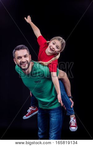 Smiling father piggybacking happy daughter and looking at camera on black