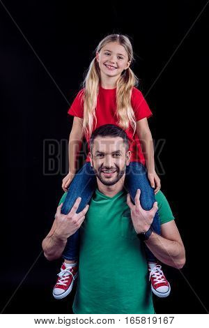 Smiling father carrying happy daughter on shoulders and looking at camera on black