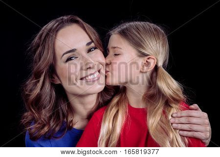 Cute little daughter kissing happy mother in cheek on black