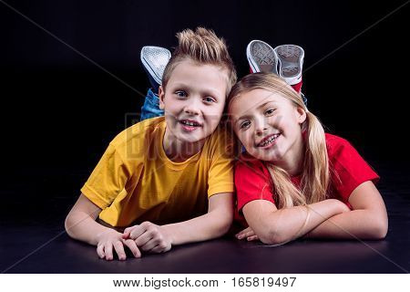 Happy siblings lying together and smiling at camera on black