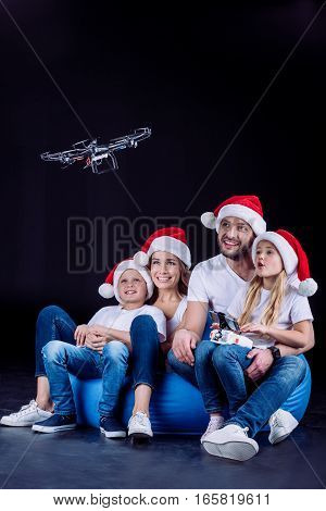 Family in Santa hats using hexacopter drone on black