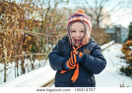 Little boy walking outdoor in the winter time and playing with snow.
