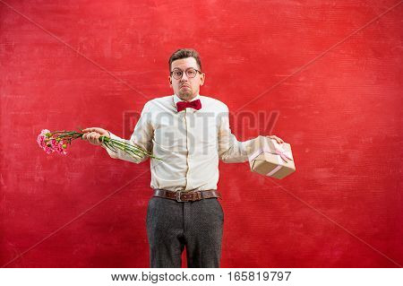 Young disappointed funny man with flowers and gift on red studio background