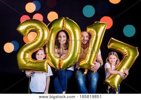 Happy family holding golden 2017 sign balloons and looking at camera on black