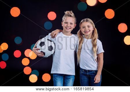 Front view of happy brother and sister posing with soccer ball on black