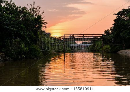 Landscape small canals water is used as a thoroughfare rural and old wooden bridge for crossing the water during sunset in Phra Nakhon Si Ayutthaya Province Thailand