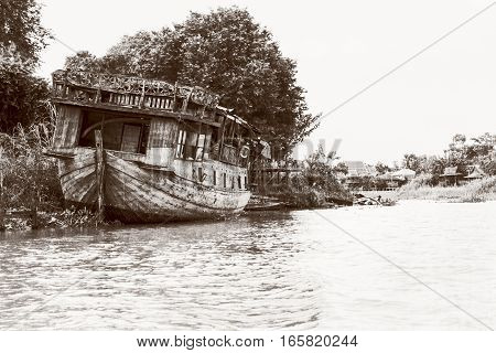 Black and white photo add texture vintage style of the old damaged wooden boat beached on the waterfront for background in Phra Nakhon Si Ayutthaya Province Thailand