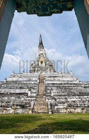 Large white ancient pagoda looking through the door frame of Wat Phu Khao Thong temple is famous tourist attraction religion Phra Nakhon Si Ayutthaya Province Thailand
