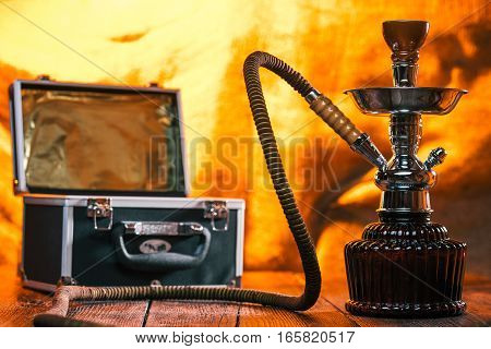 Hookah and its case over fire light background