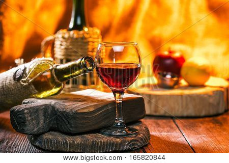 Ruby dessert wine in wineglass and sealed bottle on the foreground. Fruit and other wine bottle over fireplace light on the background