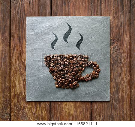 Cup from coffee beans on grey stone surface texture. Coffee shop or cafe background. Soft color toning, top view