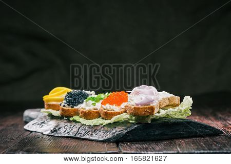 Sandwiches with white cheese and various fresh tops. Wood board serving
