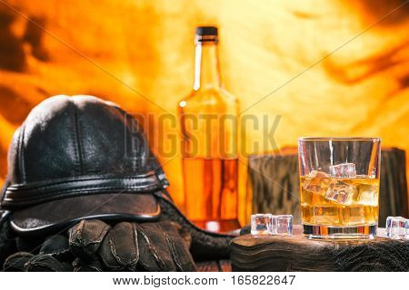 Male winter accessories: hat and gloves. Glass and bottle of whiskey over fire light background