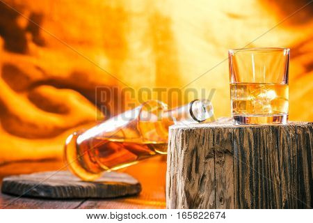 Glass and bottle of whiskey on wood stamp. Fire light background
