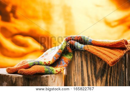 Colorful wool socks on wood stamp over fire background
