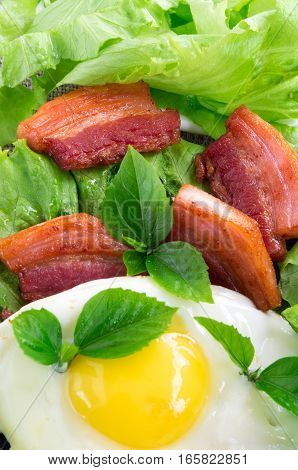 Top View On Egg Yolk, Fried Bacon And Herbs