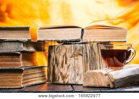 Cup of tea on rustic wood board. Stack of old books next to tea. Open book on stamp stand
