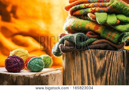 Stack of knitted wool hats, scarves and gloves on wood stand over fire background
