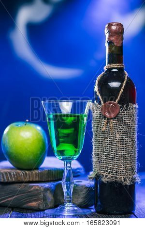 Sealed bottle of red wine, green beverage in wineglass and apple next to rustic serving boards in mysteriuos blue light