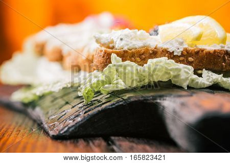 Toasts of bran bread with cottage cheese spread. Fire lighting background