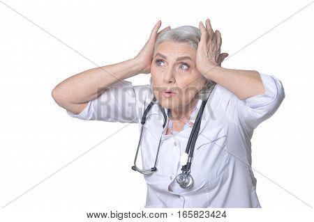 senior female doctor posing against white background