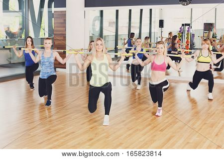Group of young women in fitness class. People making exercises. Girls do lunges with barbells. Healthy lifestyle in fitness club, intensive training