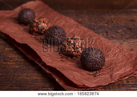 Brazilian chocolate truffle bonbon brigadeiro on wooden table. Selective focus