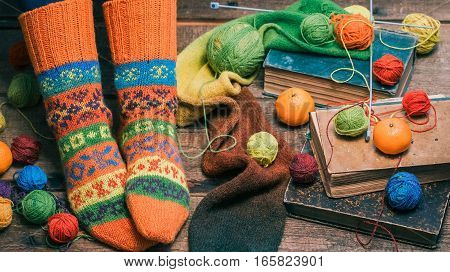 Feet of person wearing colorful winter socks sitting on the floor amid colorful yarn balls and mandarins